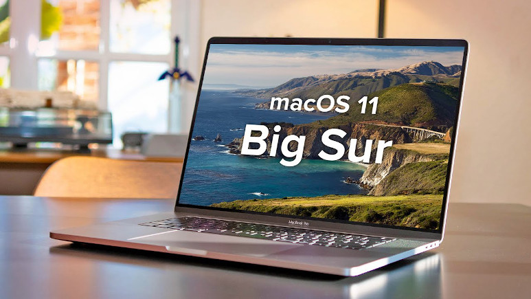 Laptop open on desk with Mac OS Big Sur text on screen
