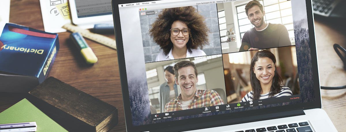 A laptop shows four people in a video conference smiling